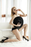 Young slim sexy topless woman in black hat against the window Stock Photography