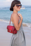 Young slim woman on the beach. Luxury handmade snakeskin in her hands. royalty free stock photo