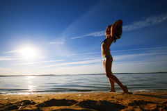 Young slim sexy woman in bikini standing on beach and looking at sunrise on the sea. Stock Images