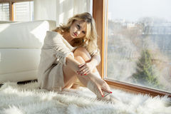 Young slim sexy woman in brown sweater against the window Stock Photography