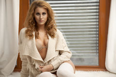 Young slim sexy woman in brown sweater against the window Royalty Free Stock Photos