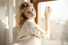 Young slim sexy woman in brown sweater against the window Stock Photo