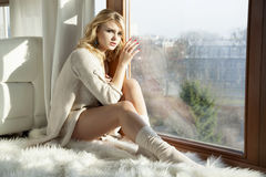 Young slim sexy woman in brown sweater against the window Stock Photos