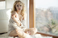 Young slim sexy woman in brown sweater against the window Royalty Free Stock Images