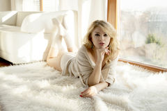 Young slim sexy woman in brown sweater against the window Royalty Free Stock Photography