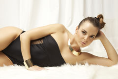 Young slim sexy woman in lingerie on the white fur Stock Photos