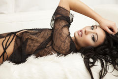 Young slim sexy woman in lingerie on the white fur Stock Image