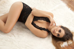 Young slim sexy woman in lingerie on the white fur Royalty Free Stock Photo