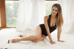 Young slim sexy woman in lingerie on the white fur Stock Photo