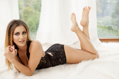 Young slim sexy woman in lingerie on the white fur Royalty Free Stock Image
