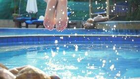 Young slim woman in pink bikini jumping into swimming pool in slow motion and water splashing on beautiful bokeh stock video