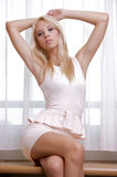 Young slim sexy woman in pink dress against the window Stock Photos