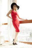 Young slim sexy woman in red dress against the window Royalty Free Stock Photo