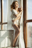 Young slim woman in white sweater against the window Royalty Free Stock Photo