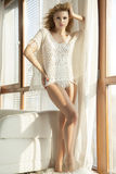 Young slim sexy woman in white sweater against the window Stock Photos