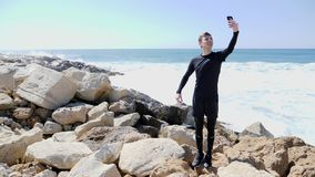 Young slim sportive happy man standing on the rocky beach and taking selfies while water splashing against the cliffs. Slow Motion.  stock video footage