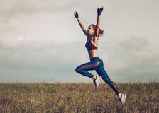 Young slim sports woman. Young happy slim sports woman running and jumping on summer field Stock Image