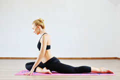 Young slim sports woman stretching indoors Royalty Free Stock Image
