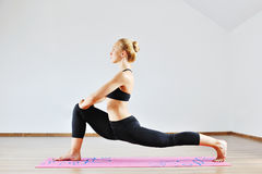 Young slim sports woman stretching indoors Stock Photo