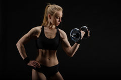 Young slim strong muscular woman posing in studio with dumbbell Royalty Free Stock Images