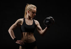 Young slim strong muscular woman posing in studio with dumbbell Royalty Free Stock Photo