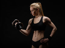 Young slim strong muscular woman posing in studio with dumbbell Stock Photos