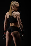 Young slim strong muscular woman posing in studio with dumbbell Royalty Free Stock Photography