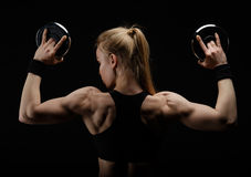 Young slim strong muscular woman posing in studio with dumbbell Royalty Free Stock Image