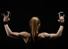 Young slim strong muscular woman posing in studio with dumbbell Royalty Free Stock Photos