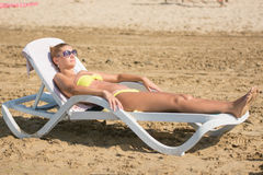 Young slim tanned girl sunbathes on beach lounger Stock Photo