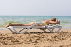Young slim tanned woman sea beach lying on deckchair face down Stock Photography