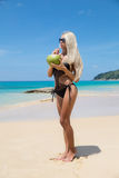 Young slim woman on beach near blue water white sand Royalty Free Stock Photography