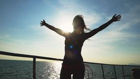Young slim woman in bikini poses on the yacht raises hands through the sun with lens flare effects enjoying her vacation. Young sexy woman pose on the yacht stock video