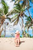 Young slim woman in bikini and straw hat on tropical beach. Beautiful girl under the palm tree on tropical Carlisle bay. Young happy woman in swimsuit on white Stock Images