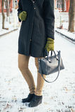 Young slim woman in a black coat and green gloves holding a hand Royalty Free Stock Images