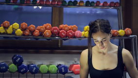 Young slim woman chatting on mobile after training in fitness center. stock video footage