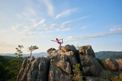Young slim woman doing complicated yoga pose on lit by summer sun top of huge rock. On green tree tops and clear blue sky background in the morning. Fitness and stock photo