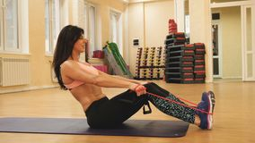 Young slim woman doing exercises with elastic fitness on mat. Fit female inflating muscles of legs and press, bending. Knees and lifting body. two hands holding stock footage