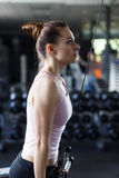 Young slim woman doing pushdown on cable machine in gym Stock Photos