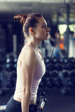 Young slim woman doing pushdown on machine in gym Royalty Free Stock Photo