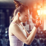 Young slim woman doing pushdown on machine in gym Stock Photography