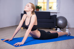 Young slim woman doing stretching exercise at home Stock Photography