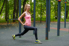 Young slim woman doing workout on training ground Royalty Free Stock Photo