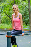Young slim woman doing workout in a training ground. In a park Royalty Free Stock Photography