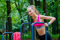 Young slim woman doing workout in a training ground Royalty Free Stock Image