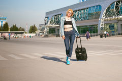 Young slim woman dressed in blue checked shirt, cap and jeans, Will depart at dawn on summer day on freedom trip with black travel royalty free stock photography