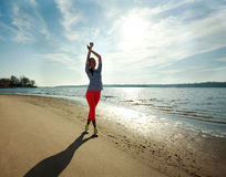 Young slim woman, exercise on the beach at sunrise Stock Image
