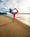 Young slim woman, exercise on the beach at sunrise Royalty Free Stock Images