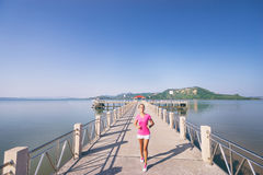 Young slim woman exercising. Healthy lifestyle. Jogging outdoors. Young slim woman exercising on the sea pier Stock Image