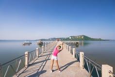 Young slim woman exercising. Healthy lifestyle. Jogging outdoors. Young slim woman exercising on the sea pier Stock Photos